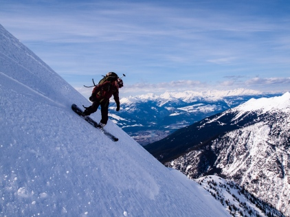 Martin rides off the top, with Revelstoke in the distance.